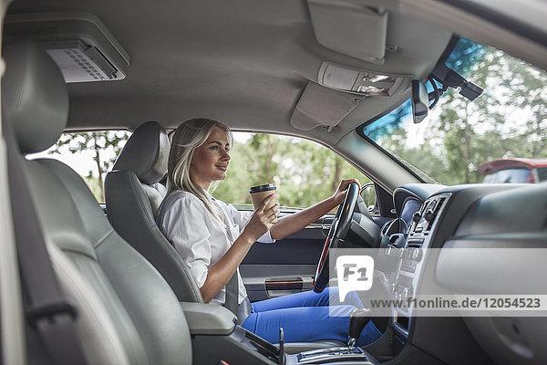 Lächelnde Geschäftsfrau hält Kaffee zum Mitnehmen und fährt Auto