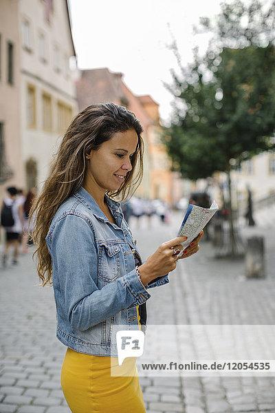 Deutschland  Rothenburg ob der Tauber  lächelnde Frau auf dem Stadtplan