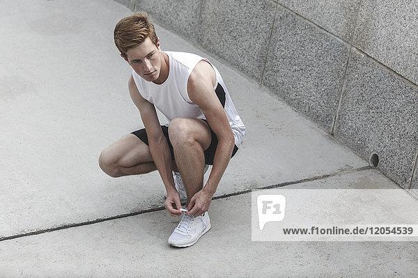 Junger Sportler beim Binden seiner Laufschuhe