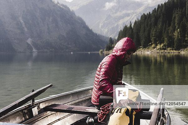 Österreich  Tirol  Alpen  Frau mit Rucksack im Boot auf dem Bergsee