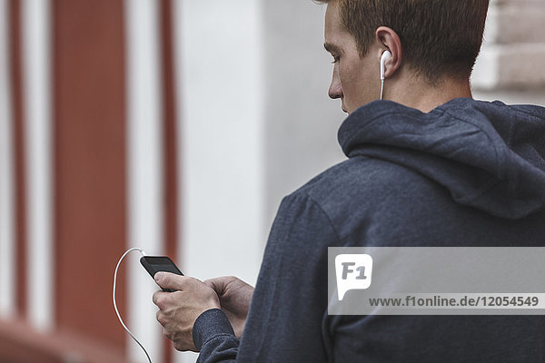 Young man with cell phone and earphones