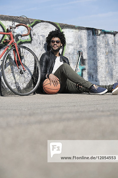 Smiling man sitting in front of grafitti wall next to his bicycle holding basketball