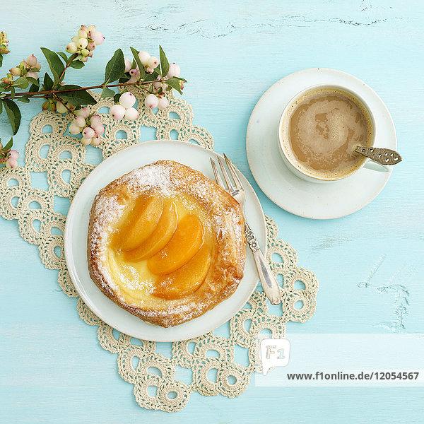 Blumen,  Kaffee und Plundergebäck mit Pfirsichen und Vanillepudding