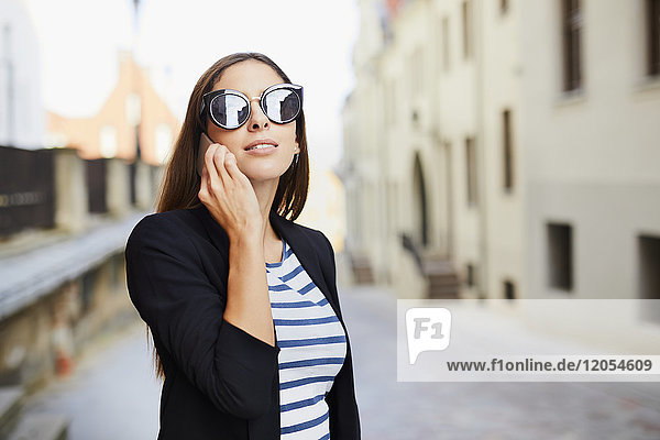 Young woman wearing sunglasses talking on phone outdoors