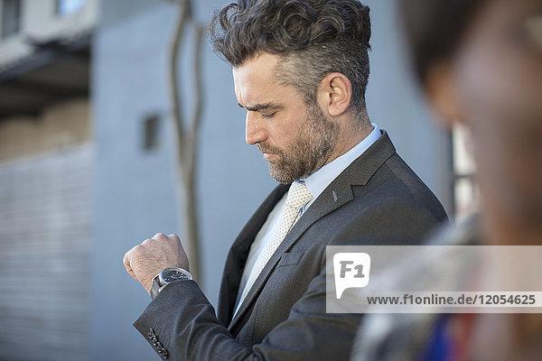 Geschäftsmann mit Blick auf seine Uhr im Freien