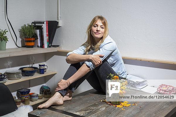 Blonde Frau zu Hause auf Holztisch sitzend