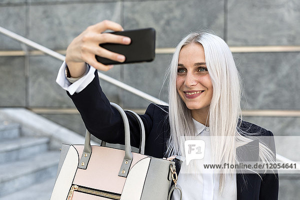 Smiling young woman ctaking a selfie on stairs in the city