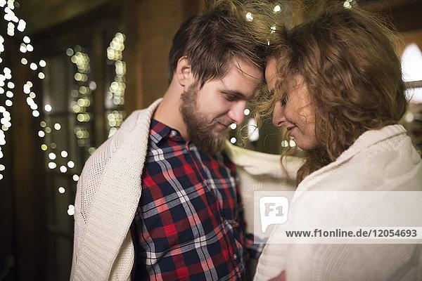 Junges Paar in eine Decke gehüllt  die nachts draußen kuschelt.