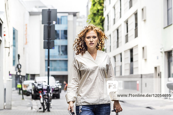Portrait of young woman with suitcase and smartphone in the city