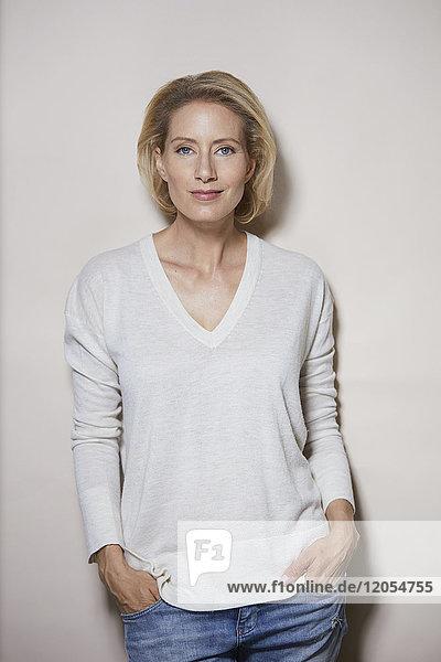 Porträt einer lächelnden blonden Frau vor hellem Hintergrund