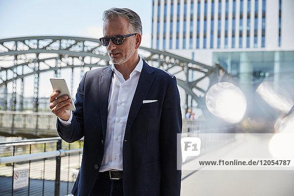Deutschland  München  Portrait eines Geschäftsmannes mit Sonnenbrille auf dem Handy