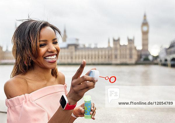 UK,  London,  glückliche Frau macht Seifenblasen in der Nähe von Palace of Westminster