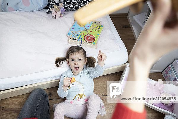 Kleinkind Mädchen  das auf Mutters Hand zeigt und ein Spielzeugflugzeug hält.