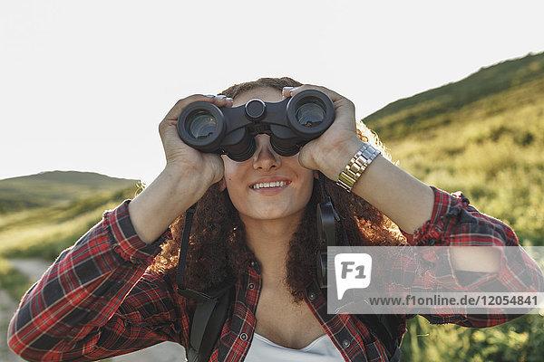Teenager Mädchen mit Rucksack mit Fernglas in der Natur