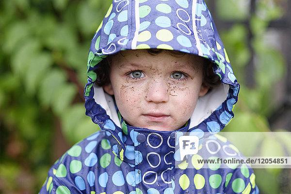 Portrait of little boy with dirty face wearing hooded jacket in rain