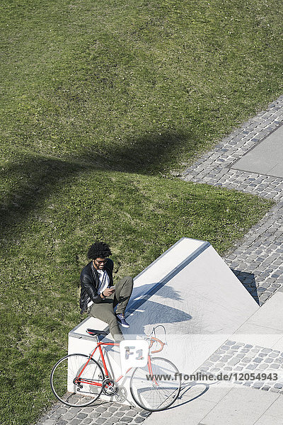 Man sitting in city skatepark with smartphone next to his bicycle