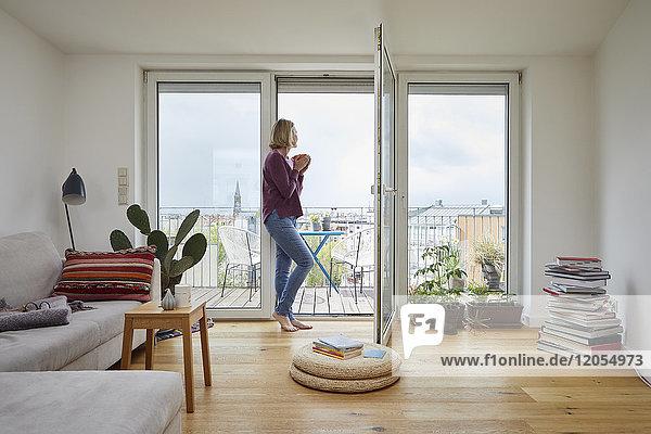 Reife Frau zu Hause mit Blick aus dem Balkonfenster