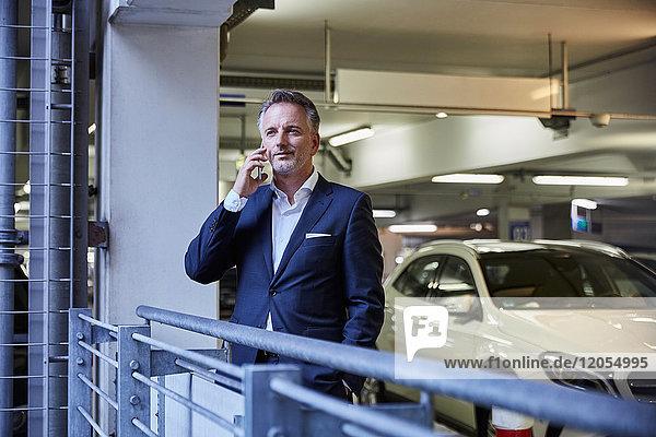 Geschäftsmann mit Smartphone im Parkhaus
