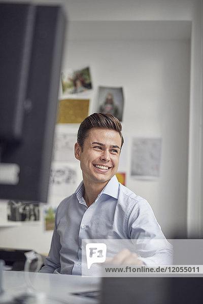 Porträt des lachenden jungen Geschäftsmannes am Schreibtisch im Büro
