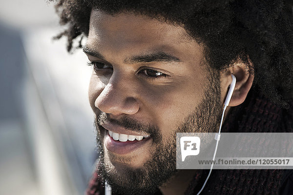 Portrait of smiling man listening to music on his earphones