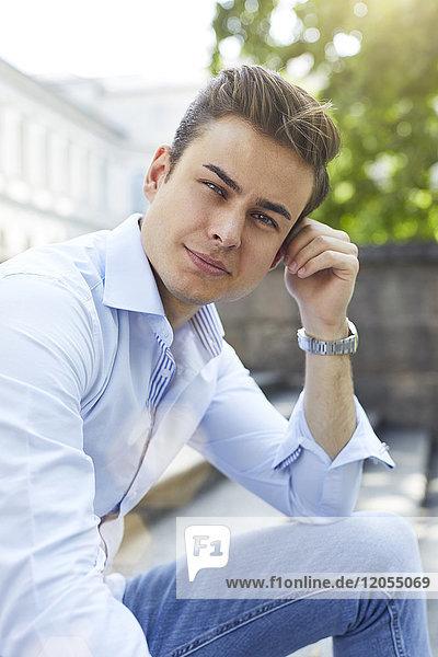 Porträt eines nachdenklichen jungen Mannes  der auf einer Treppe sitzt.