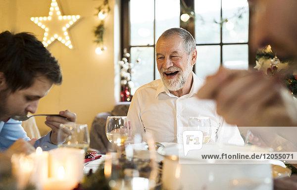 Glücklicher älterer Mann  der den erwachsenen Sohn am Weihnachtstisch anschaut.