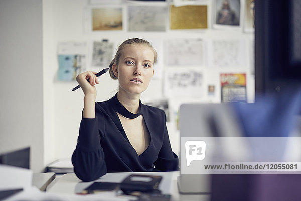 Porträt einer jungen Geschäftsfrau am Schreibtisch im Büro