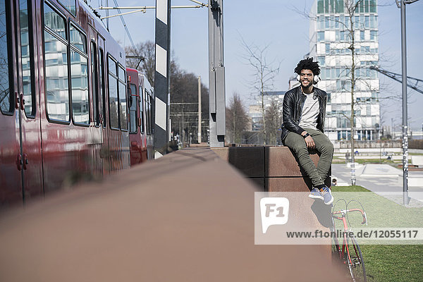 Smiling man sitting on wall listening to music next to passing train