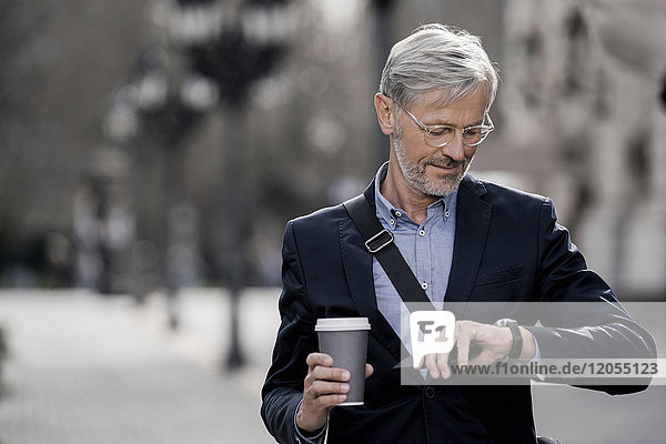 Grey-haired businessman in the city looking at watch holding coffee to go