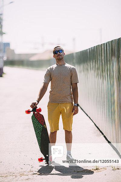 Portrait eines selbstbewussten jungen Mannes mit Longboard