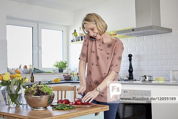 Reife Frau bereitet einen Salat zu und telefoniert in der Küche.