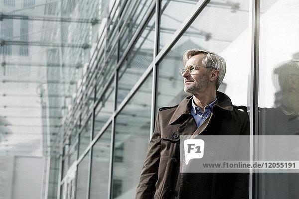 Grauhaariger Geschäftsmann an der Glaswand stehend