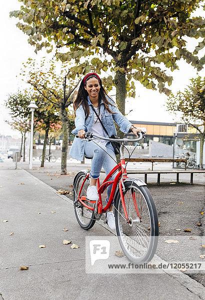 Spanien  Gijon  junge Frau beim Radfahren in der Stadt