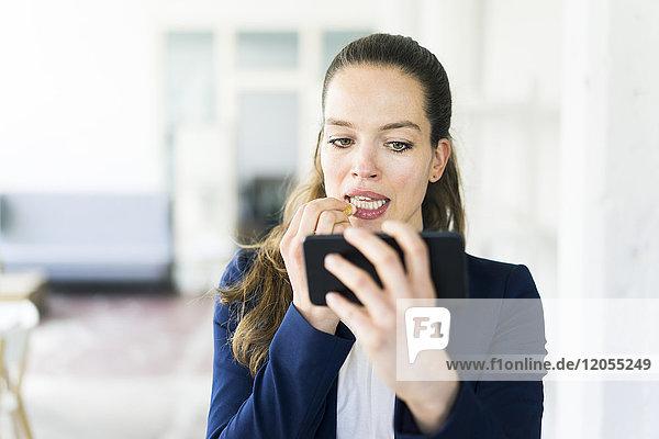 Geschäftsfrau mit Handy und Lippenstift