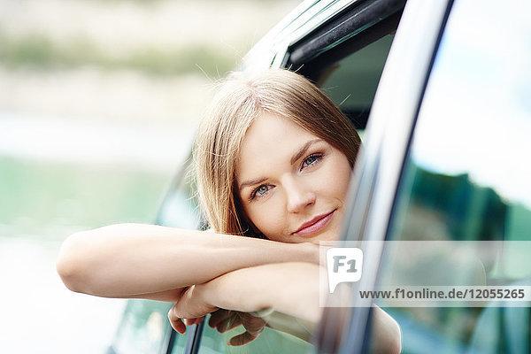 Porträt einer jungen Frau  die sich aus dem Autofenster lehnt.