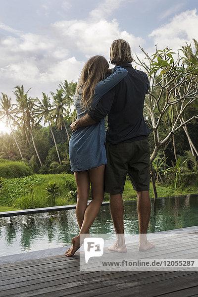 Umarmendes Paar  das auf einer Holzterrasse vor dem Pool steht und einen atemberaubenden Blick auf den Sonnenuntergang in einem üppigen tropischen Garten genießt.