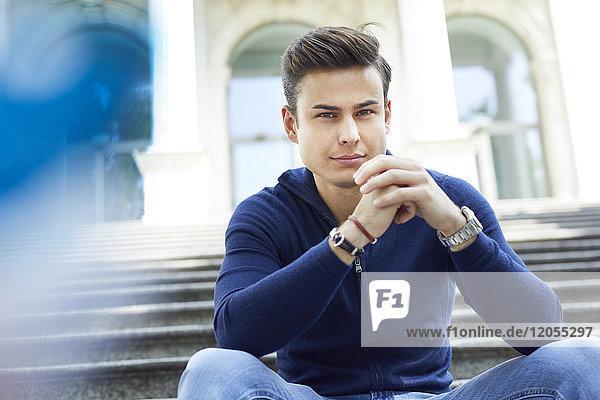 Porträt eines ernsthaften jungen Mannes  der auf einer Treppe sitzt.