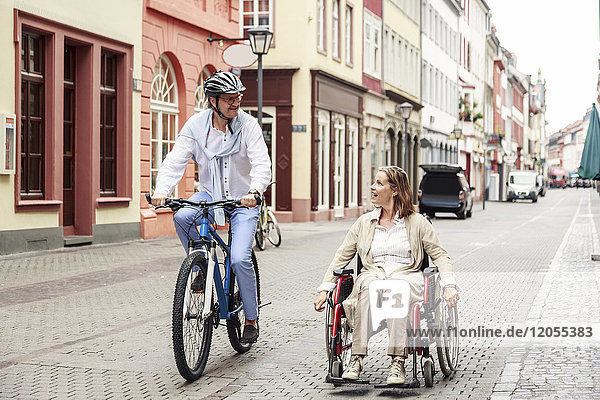 Germany  Heidelberg  woman in wheelchair and man on bicycle in the city