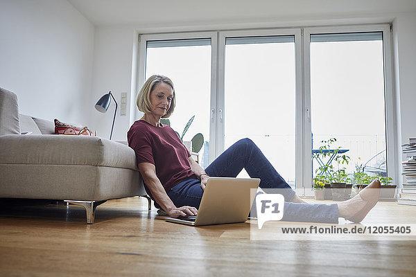 Reife Frau zu Hause mit Laptop auf dem Boden