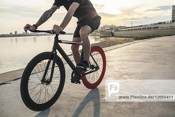 Junger Mann auf Fixie Bike am Wasser bei Sonnenuntergang