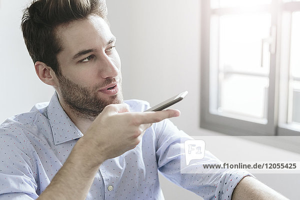 Young businessman working in office  using smartphone