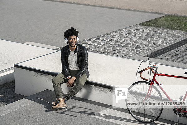 Smiling man listening to music on headphones next to his bicycle