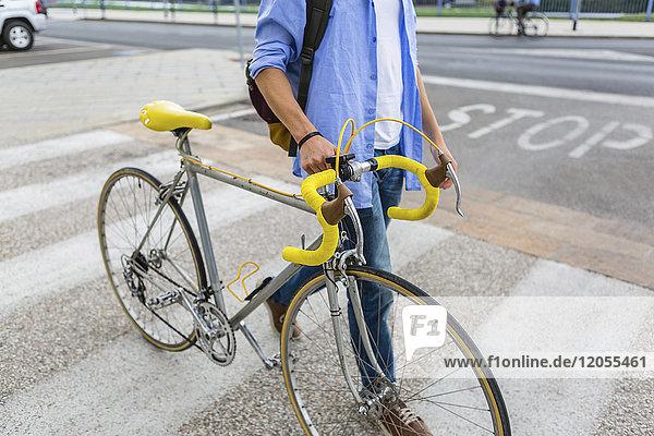 Junger Mann schiebt sein Fahrrad auf Zebrastreifen  Teilansicht