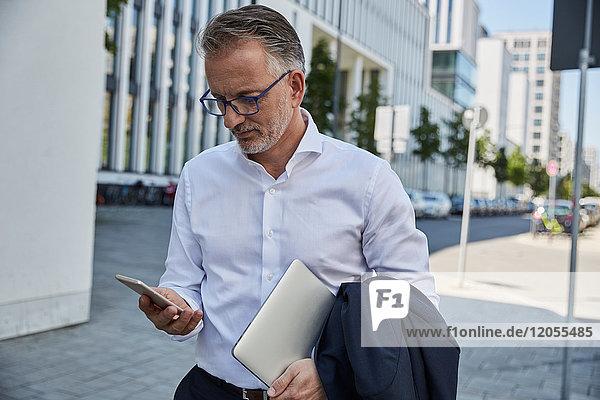 Geschäftsmann mit Laptop beim Blick aufs Handy