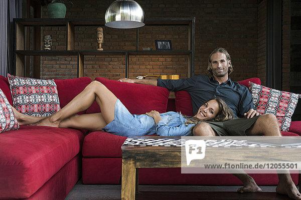 Lächelndes Paar auf roter Couch im modernen Wohnzimmer