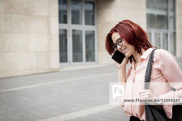Junge Geschäftsfrau in der Stadt beim Telefonieren