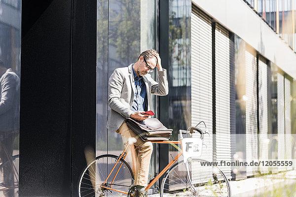 Schockierter Geschäftsmann auf dem Fahrrad beim Blick aufs Handy