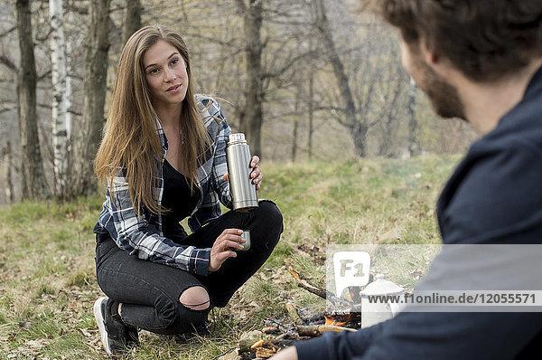 Frau am Lagerfeuer mit Blick auf den Mann im Wald