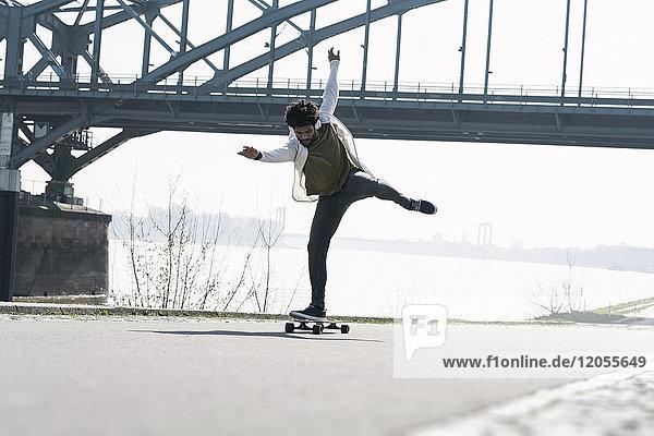 Young man balancing on longboard at the riverside