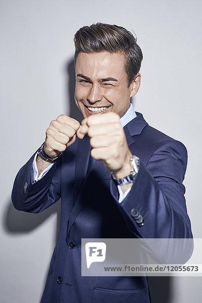 Porträt des lachenden jungen Geschäftsmannes Boxen
